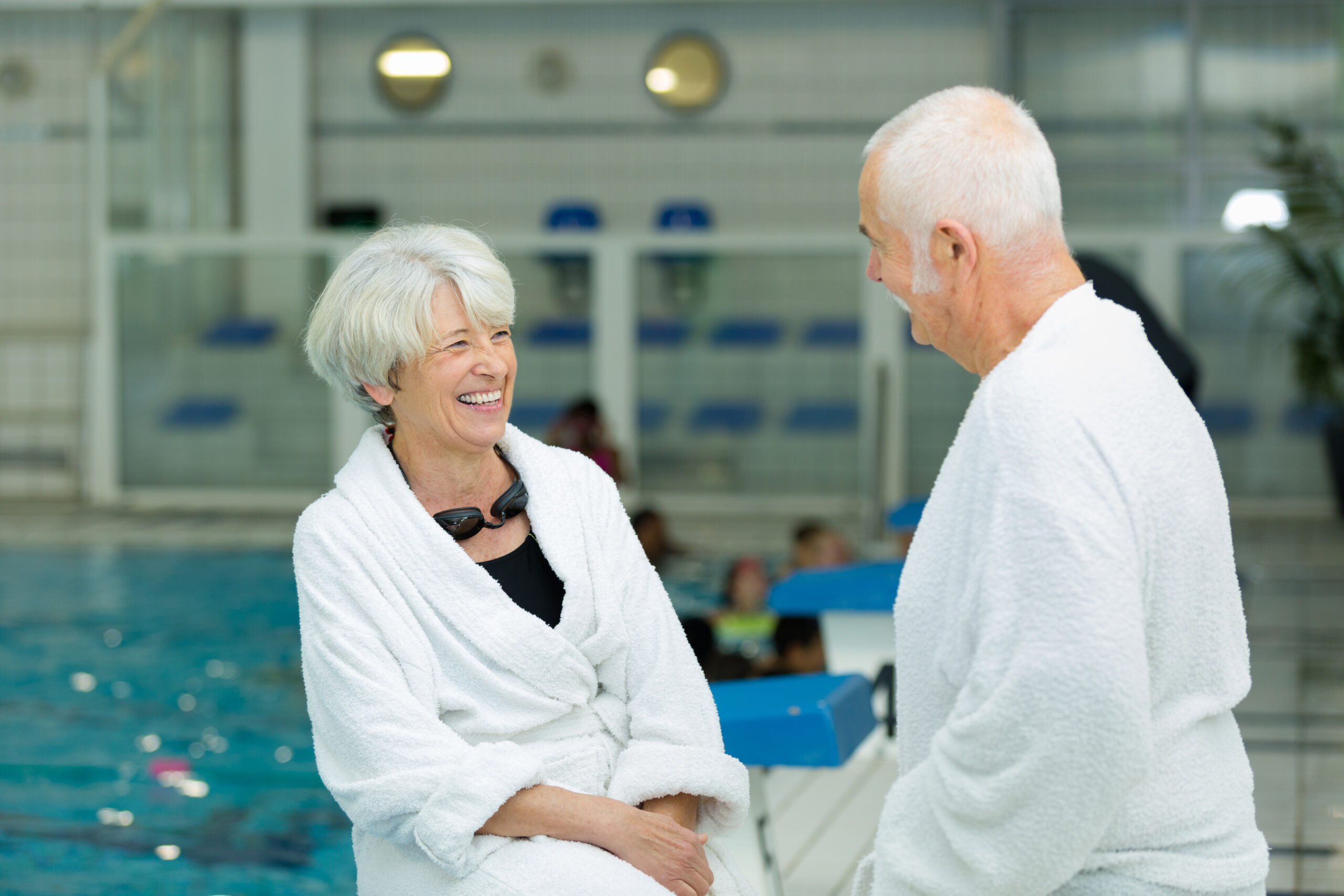 senior couple wearing bathrobes laughing by side of indoor pool